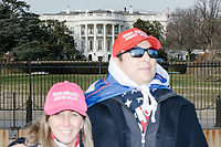 Eric Villacis, 41, of Atlanta, Georgia, (right) and Lola Lopez, 45,  wear Make America Great Again hats as they pose for pictures outside the White House in Washington, D.C., on Jan. 19, 2017, the day before the inauguration of president-elect Donald Trump.