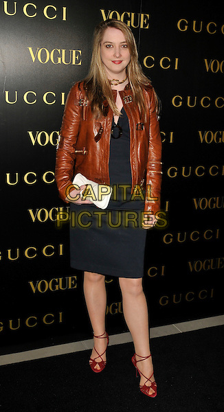 DAISY DE VILLENEUVE.A dinner in honour of Frida Gianni, Creative Director of Gucci, hosted by Alexandra Shulmanand at the Saatchi Gallery, Duke of York's Headquarters, King's Road, Chelsea, London, England..April 1st, 2009 .Vogue full length brown leather jacket black dress red strappy sandals shoes .CAP/CAN.©Can Nguyen/Capital Pictures.