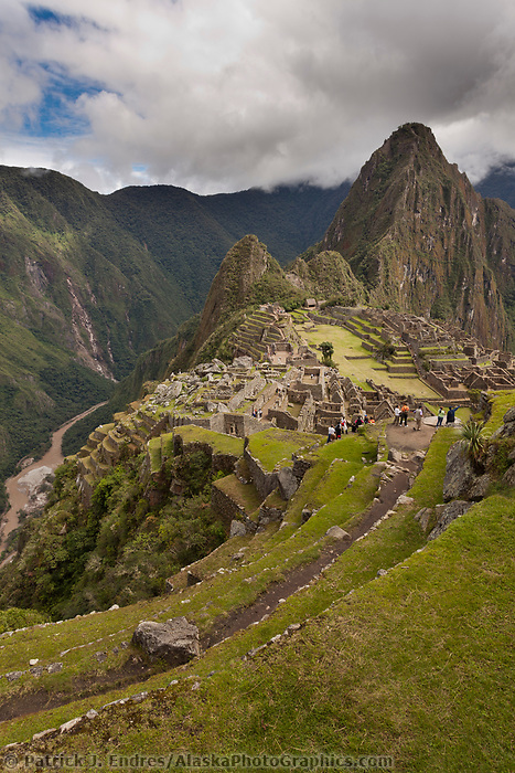 """Huayanapichu (young mountain) in the distance at Machu Picchu, the ancient """"lost city of the Incas"""", built about 1400 CA. Discovered by Hiram Bingham in 1911. Urubamba river in the distance."""