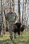 Hunter, holding shotgun, with harvested wild turkey