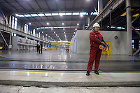 A worker operates a large lift to move newly made rolls of steel sheets at Ma Steel's new plant in Maanshan, China..29 Dec 2008.