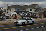 New Jersey, United States. 25th Feb, 2013 -- A police car drive in front of a home destroyed almost 4 months ago by Sandy Storm at Jersey Shore in New Jersey. Photo by Eduardo Munoz Alvarez / VIEWpress.