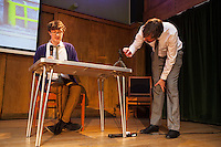The Boring Conference at Conway Hall. James Ward helps adjust the camera that will create a live feed of Jason Ward (no relation) as he does a crossword puzzle on stage. The Boring Conference is a one-day celebration of the mundane, the ordinary, the obvious and the overlooked; subjects often considered trivial and pointless, but when examined more closely reveal themselves to be deeply fascinating.<br /> <br /> It was created in response to the cancellation of the 2010 Interesting Conference. It seemed like the obvious thing to do.