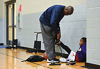"""Allen Thompson of Fayetteville (from left) ties Aiden Thompson's shoes, Sunday, February 9, 2020 during a basketball tryout at Rogers High School in Rogers. Check out nwaonline.com/200210Daily/ for today's photo gallery.<br /> (NWA Democrat-Gazette/Charlie Kaijo)<br /> <br /> Coach Chad Neipling started a new AAU (Amateur Athletic Union) basketball team called the NWA Devils to provide young basketball players opportunities to build their fundamentals and conditioning in the sport and compete against other AAU teams at a national level. The program gives kids national recognition, tracks player stats and attracts attention from coaches.<br /> <br /> Neipling and other parents wanted additional basketball programs for their kids but found problems in other programs they tried so he started his own. """"Our kids played competitively together. We had been a part of some organizations Where we had to pay a lot of money to get our kids there. Sometimes we'd show up and we didn't have a facility or we went to a tournament and we weren't in the tournament. There wasn't a focus on the fundamentals. A lot of it we felt like was a money grab.""""<br /> <br /> After selecting the players for the team, they will prepare for their first tournament in March. He wants to provide competitive opportunities for the kids but also ensure they grow to be good people. """"We're gonna do some community service. We'll go out and go to the Arkansas food bank,"""" he explained to the kids before starting the tryout. """"I want you to go out in the community and be seen. It's about building great people before a great basketball player."""""""
