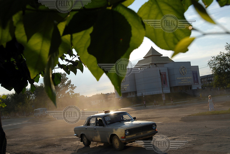 A taxi drives in front of a new museum in Kyzyl.