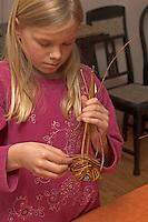 Kinder flechten Nistkugel für Vögel, Vogel, Nisthilfe, Nest, Kugelnest. Mädchen, Kind verflechtet dünne Zweige
