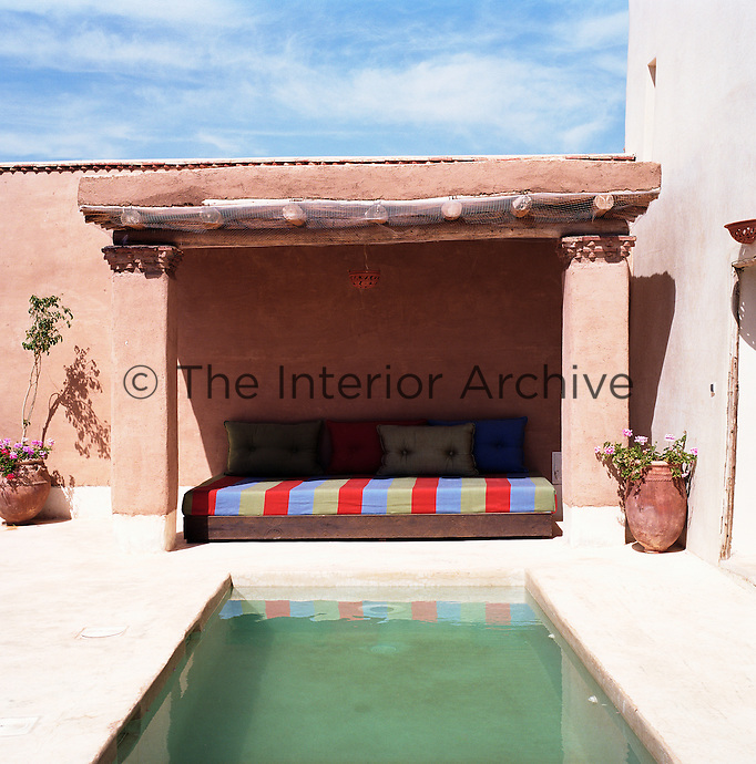 A banquette under a rustic awning at one end of a plunge pool on a private terrace