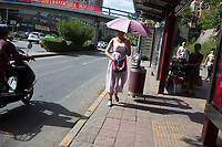 A woman carrying a parasol walks next to a street in Xian, Shaanxi, China.