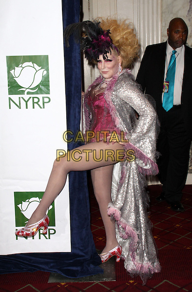 BETTE MIDLER.Bette Midler's New York Restoration Project Annual Hulaween Gala held at the Waldorf-Astoria Hotel,New York, NY, USA, 30th October 2009..Halloween full length costume dressed-up outfit hands on hip leg kicking silver coat pink black feathers red shoes leotard knee sequin sequined .CAP/ADM/PZ.©Paul Zimmerman/Admedia/Capital Pictures