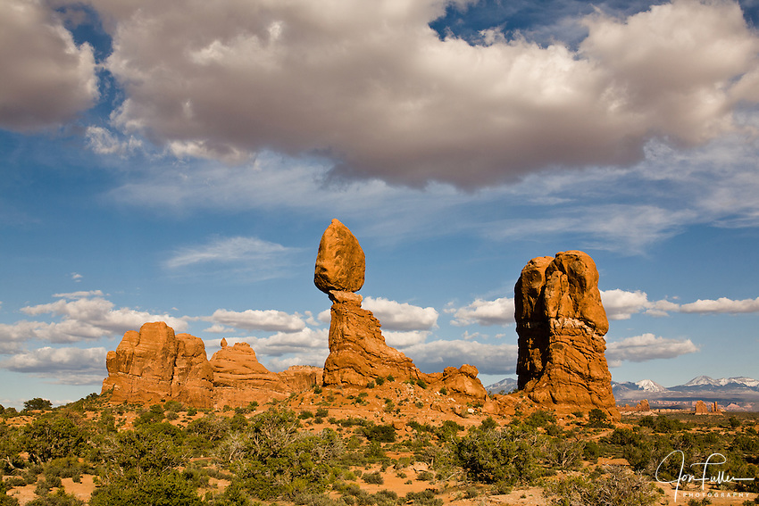Afternoon at Balanced Rock in Arches National Park, Moab, Utah, USA with sunny, blue skies and cumulus clouds.