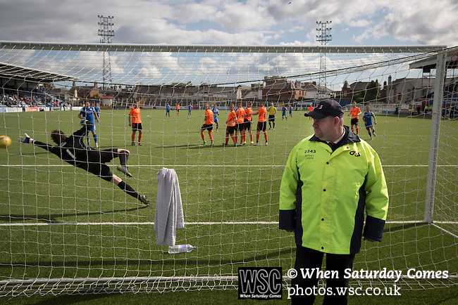 Queen of the South 2 Stranraer 0, 11/08/2015. Scottish Challenge Cup first round, Palmerston Park. A steward standing guard is oblivious to Ryan Conroy scoring his team's decisive second goal at Palmerston Park, Dumfries, as Queen of the South (in blue) host Stranraer in a Scottish Challenge Cup first round match. The game was the opening match of the season in a competition open to sides below the Scottish Premiership. Queen of the South won the match 2-0, watched by a crowd of 1229 spectators. Photo by Colin McPherson.