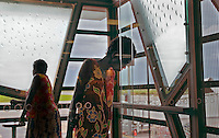 Aborigine women wait in the Darwin airport for a flight to Maningrida.  Ancient rock art isn't that different from the raindrops etched in the modern glass of the Darwin airport--just man trying to describe the natural world.