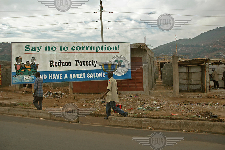 'Say no to corruption - reduce poverty' - poster on the roadside.
