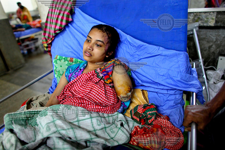 18 year old Shapla was on the third floor of the Rana Plaza complex when it collapsed. She lost the lower part of her left arm and has a number of other injuries. She had been working in a textile factory in the complex for three years. She sometimes cannot remember her own name after the accident. Her husband Mehedul was trapped in the building for 72 hours but was rescued without any injuries. The 8 storey Rana Plaza complex, which housed a number of garment factories employing over 3,000 workers, collapsed on 24 April 2013. By 29 April, at least 380 were known to have died while hundreds remained missing. Workers who were worried about going to work in the building when they noticed cracks in the walls were told not to worry by the building's owner, Mohammed Sohel Rana, who is a member of the ruling Awami League's youth front. He fled his home and tried to escape to neighbouring India after the building collapsed but was caught by police and brought back to Dhaka. Some of the factories working in the Rana Plaza building produce cheap clothes for various European retailers including Primark in the UK and Mango, a Spanish label. The final death toll was 1,127. /Felix Features
