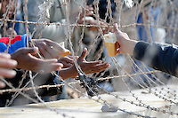 Bread is passed to refugees through barbed wire on the border between Tunsia and Libya. Tens of thousands of people, mainly Egyptian workers, fled unrest in Libya and crossed the border into Tunisia. Some slept in the open for several days before being processed.  At the same time forces loyal to Col. Gaddafi fought opposition forces in various parts of the country.