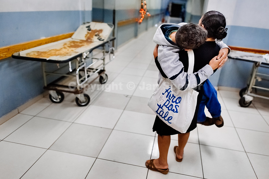 A Salvadoran woman carries his ill son while seeking an urgent medical help in the emergency department of a public hospital in San Salvador, El Salvador, 22 December 2015.