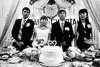 Kazakhstan. Aralsk. Kazakh wedding. The muslim bride wears a white wedding dress while the groom has a black suit and a tie. The new couple stands up with on both sides their witnesses (best man (L) and woman (R)). Food and cakes with a plastic heart on the table. Aralsk is located in the Kyzyl Orda Province. © 2008 Didier Ruef ..