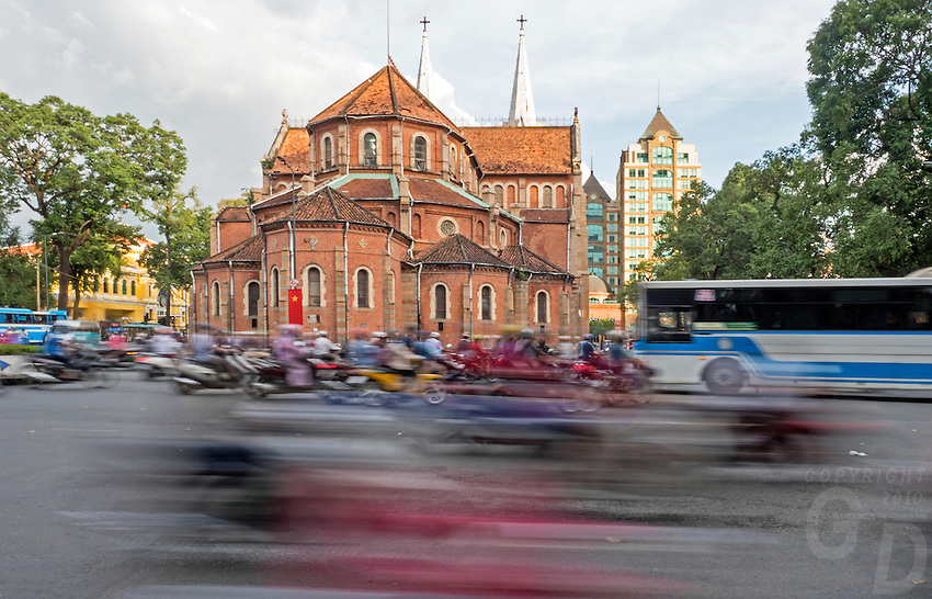 The Notre-Dame Cathedral Basilica of Saigon and Street Life in Saigon or in Vietnamese Ho Chi Minh City where old and new architecture mix in harmony. The bustling Metropolis of South Vietnam.
