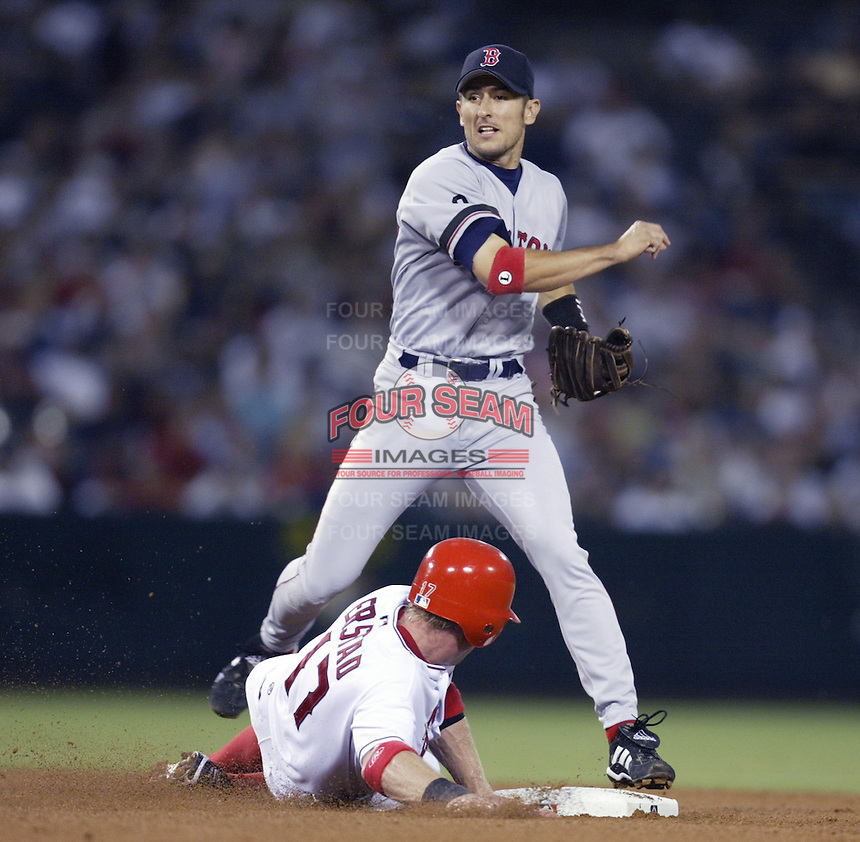 Nomar Garciaparra of the Boston Red Sox throws to first base after forcing out Darin Erstad of the Los Angeles Angels at second base during a 2002 MLB season game at Angel Stadium, in Anaheim, California. (Larry Goren/Four Seam Images)