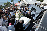 In the shadow of the ruined Cathedral of Our Lady of the Assumption, Haitians held a January 23 funeral mass for the Roman Catholic archbishop and vicar general of Port-au-Prince, both of whom were killed in the country's earthquake. With Haitian President Rene Preval in attendance, church officials and ordinary Haitians said goodbye to Archbishop Joseph Serge Miot, who died when the impact of the January 12 quake hurled him from a balcony, and Msgr. Charles Benoit, the vicar general whose body was pulled from the cathedral debris. Here the archbishop's casket is placed in a vehicle for transport to the cemetery.