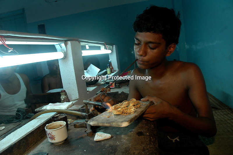 An Indian young boy working with a blower and flame to give the gold ornament the right shape. Kolkata, India  6/13/2007  Arindam Mukherjee