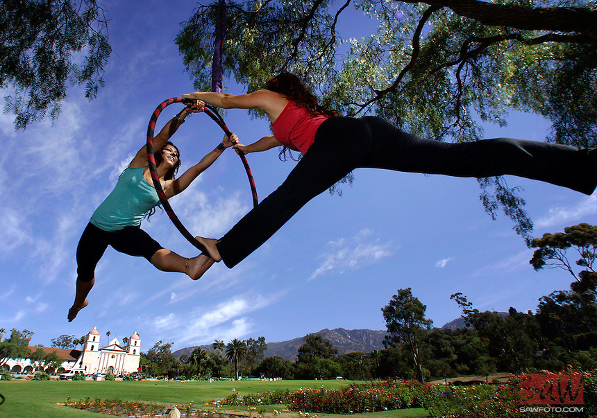 SANTA BARBARA,CA - AUGUST 5,2009: Veronika Petra, left, and Alysia James, right, practice an arial hoops routine for a performance from a tree in the Santa Barbara Mission's rose garden, August 5, 2009. The pair will be at the World Renaissance Faire this weekend at Irvine Lake, Silverado, Ca.