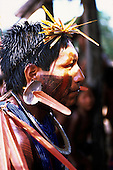 Bacaja village, Brazil. Xicrin Kayapo man with shell and feather ear decorations, bead necklaces and face paint.