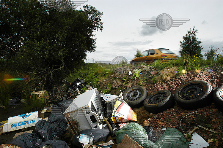 Fly-tipping - rubbish dumped beside a rural road.