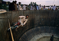 A man rides a bicycle in circles inside a wooden barrel defying gravity in the act known as the Wheel of Death. The circus act is part of a camel celebration and festival.