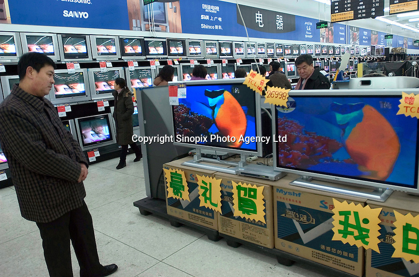 A man looks at TV setts in a newly opened Wal-Mart Supercenter in Harbin, Heilongjiang province, China..27-DEC-04