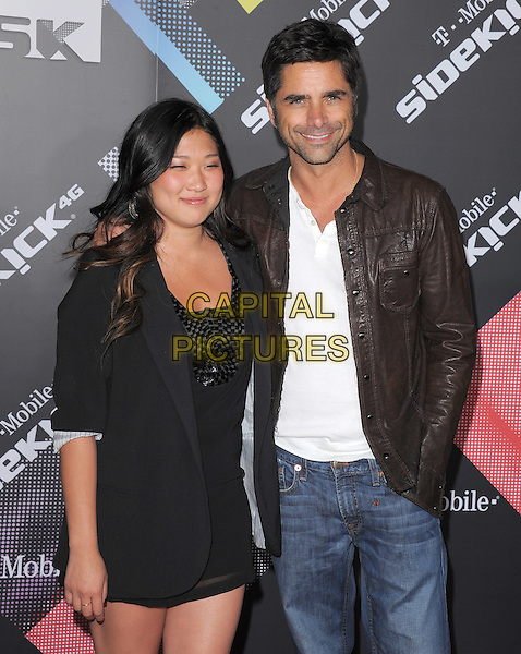 JENNA USHKOWITZ & JOHN STAMOS .at The T-Mobile Sidekick 4G Launch Party held at a private lot in Beverly Hills, California, USA, April 20th 2011..half length black jacket blazer dress arm around jeans brown leather  .CAP/RKE/DVS.©DVS/RockinExposures/Capital Pictures.