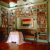 Built-in bookcases painted a cool pistachio green contrast with the deep red tones of the polished wooden floorboards in the library