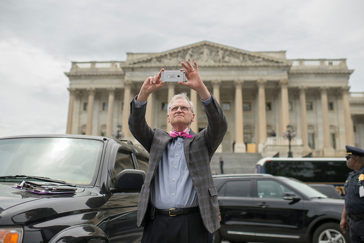 UNITED STATES - MAY 4: Rep. Earl Blumenauer, D-Ore., photographs protesters on the East Front of the Capitol after the House passed the Republicans' bill to repeal and replace the Affordable Care Act on May 4, 2017. The protesters support the ACA. (Photo By Tom Williams/CQ Roll Call)