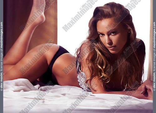Glamour portrait of a sexy young beautiful woman in lingerie posing on a bed