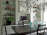 Comfortably seating eight, the long dining table is lit by a matching pair of ethereal-looking chandeliers