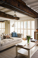 Two sets of French windows with louvred shutters provide pleasingly diffuse light in the living room whilst also providing maximum privacy