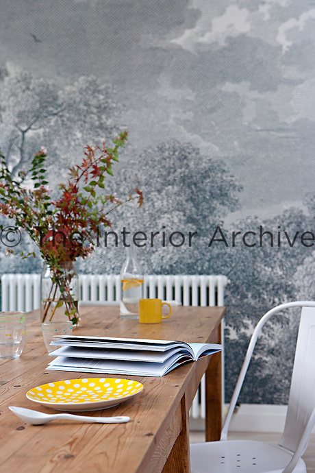 The kitchen/dining extension was built into the garden, making the grisaille wallpaper that covers one wall all the more appropriate
