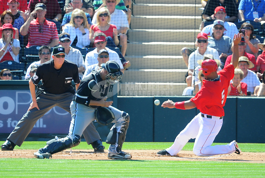Mar. 6, 2012; Tempe, AZ, USA; Los Angeles Angels base runner Albert Pujols slides safely into home to score as Chicago White Sox catcher Tyler Flowers drops the ball in the first inning during a spring training game at Tempe Diablo Stadium.  Mandatory Credit: Mark J. Rebilas-