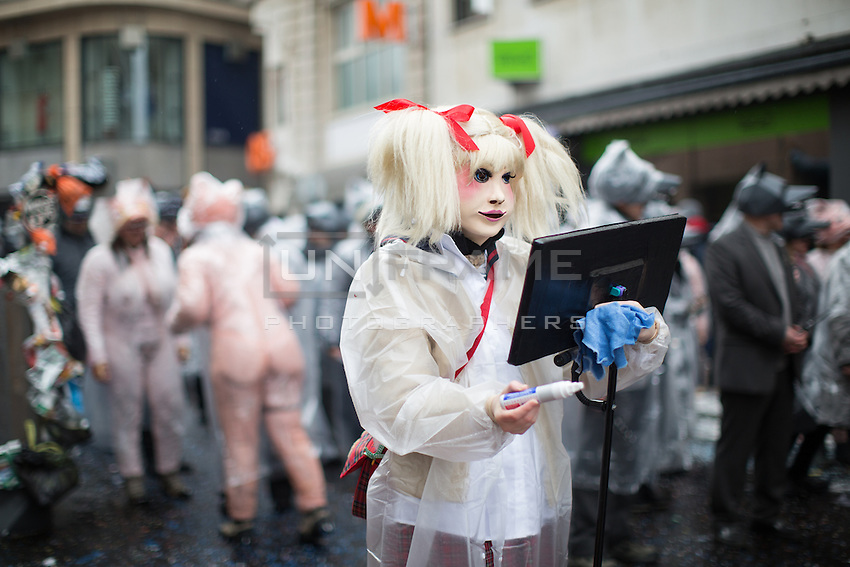 A masked participant holds a marker and whiteboard during a procession or Cortège on the first day of Fasnacht, the Carnival of Basel, in Switzerland. Feb. 23, 2015.