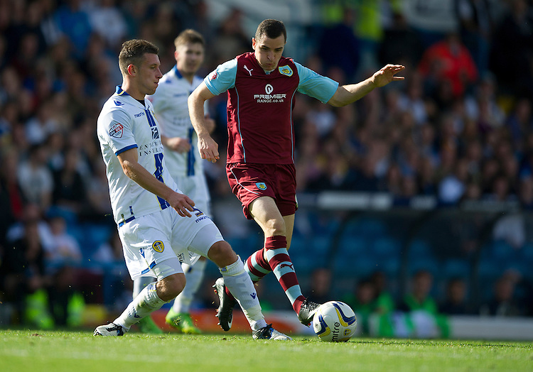 Burnley's Dean Marney just toe pokes the ball away from Leeds United's Jason Pearce<br /> <br /> Photo by Stephen White/CameraSport<br /> <br /> Football - The Football League Sky Bet Championship - Leeds United v Burnley - Saturday 21st September 2013 - Elland Road - Leeds<br /> <br /> &copy; CameraSport - 43 Linden Ave. Countesthorpe. Leicester. England. LE8 5PG - Tel: +44 (0) 116 277 4147 - admin@camerasport.com - www.camerasport.com