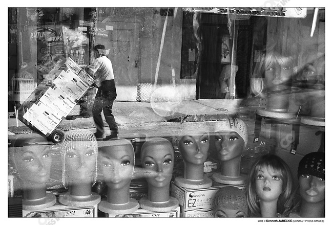 Reflections in the window of a clothing store in border town,  Laredo, Texas. Most of the downtown businesses depend on and cater to Mexican customers. Laredo, Texas, March 2003.