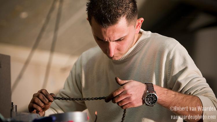 Adnan Akyüz repairs a chain in preparation for the long ride to Amsterdam.