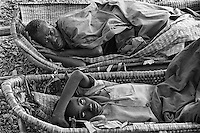 A Rwandan woman, top, (Elizabeth Nyiramariro) and a boy (Jean Paul Ndanguzi) lie in basket-like litters awaiting care from medical personel of the AmeriCares clinic in Buranga, Rwanda, October 1994. The New Canaan Connecticut humanitarian organization set up their clinic on the road between Goma, Zaire (now Congo) and Kigali, Rwanda to help refugees returning from the camps in Goma and the people living in the area whose illnesses resulted from the destruction of what little infracstracture existed before civil war. (photo Rick D'Elia)