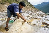 Peru.  Maras Salt Pans, Urubamba Valley.  Man Collecting Salt.