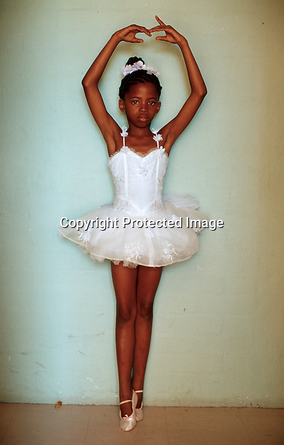 "Wongi Zoe, age 8, has danced for 3 years in the ""Dance for all"" programme and is waiting to enter the stage at a yearly performance on November 25, 2000 in Guguletu, South Africa. The programme was started by the Cape Town city ballet in the poor and destitue squatter camps nine years ago. About 200  kids aged from 6-18 are dancing and finding something meaningful to do after school. .Photo: Per-Anders Pettersson (ppettersso@aol.com)"