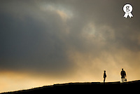 Silhouettes of two people standing on horizon, dusk (Licence this image exclusively with Getty: http://www.gettyimages.com/detail/200472176-001 )