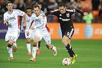 Washington, D.C.- March 29, 2014. Fabian Espindola (9) of D.C. United run with the ball from A.J. Soares (5) of the New England Revolution.  D.C. United defeated the New England Revolution 2-0 during a Major League Soccer Match for the 2014 season at RFK Stadium.