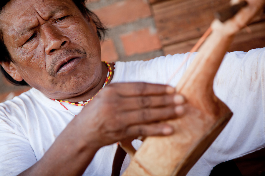 Ramon Duarte, spiritual and cultural elder of katupyry village near San Ignacio, Misiones, Argentina, tuning a violin he has made by hand using a kinfe and machete.