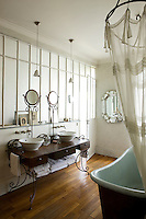 In the bathroom the ornate double washstand is a design by Liana Yaroslavsky and the entire wall behind consists of frosted glass panels