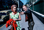 Punk helping passer by on Kings road Chelsea London woman sticking tongue out at photographer 1980s Uk
